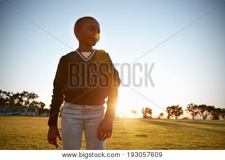 African elementary school girl in a park at sunset, close up