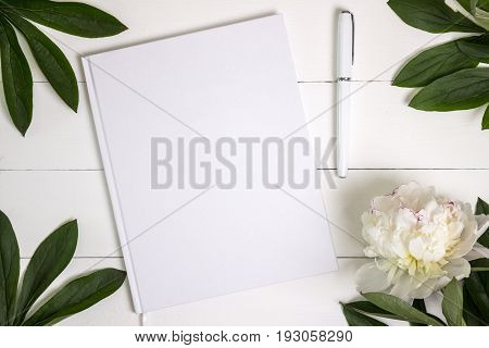 Blank white book journal wedding guestbook notebook mockup. Object for design and branding. White peony and wooden texture top view.