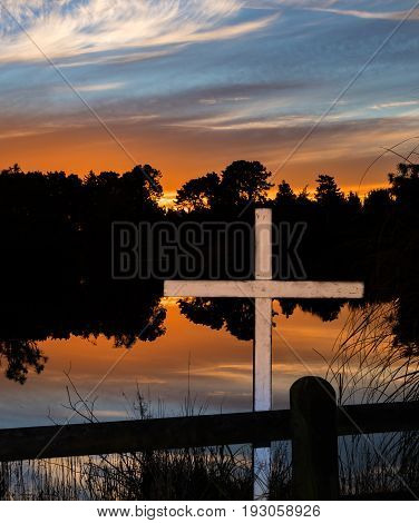 White cross by a lake at sunset.