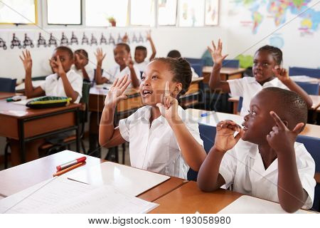 Kids showing hands during a lesson at an elementary school