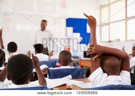 Kids raising hands to answer teacher at an elementary school lesson