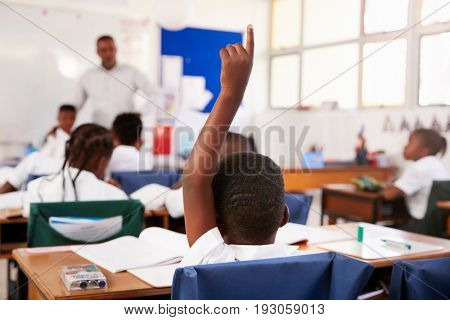 Child raising hand to answer in an elementary school lesson
