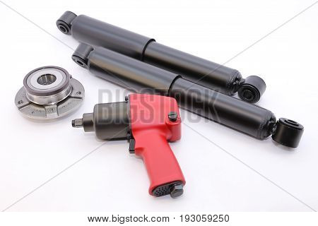 Car dampers and pneumatic impact wrench on white background isolation