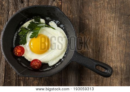 Black cast iron frying pan with fried egg on rustic wood background