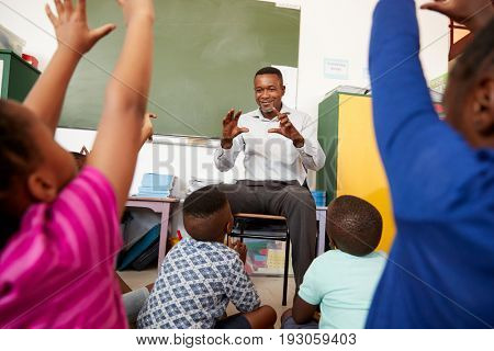 Elementary school kids sitting on floor listening a teacher