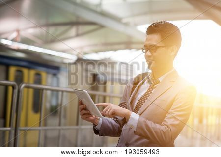 Asian businessman using digital tablet pc while waiting commuter, with beautiful sun flare at background.