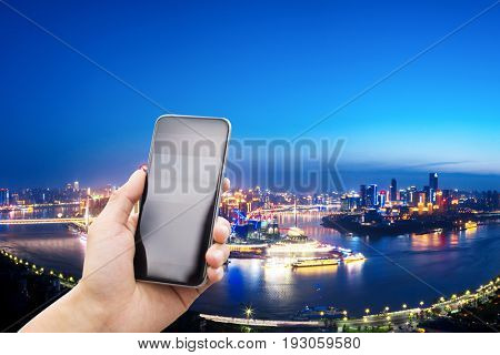mobile phone with cityscape of chongqing at night