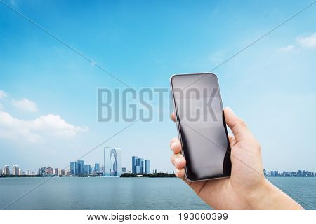 mobile phone with modern buildings near water in suzhou