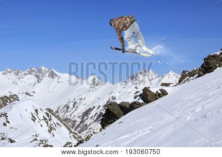 Flying skier in the mountains. Extreme freeride sport.