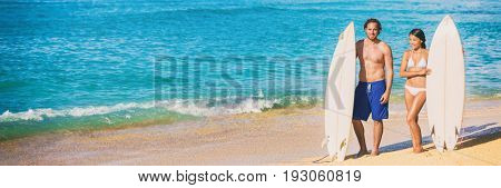 Beach surfing vacation banner surfers people fitness lifestyle couple with surfboards ready to surf on blue ocean background. Summer travel holidays.