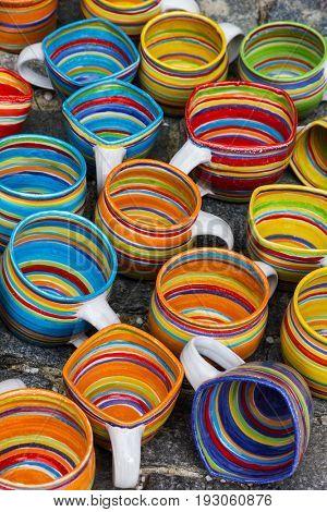 Colorful ceramic mugs at market.