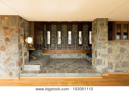 Frontal view of  stone living with design lamp. Nobody inside