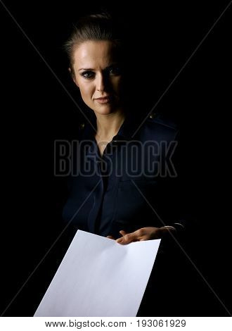 Coming out into the light. Portrait of woman in the dark dress isolated on black giving paper sheet