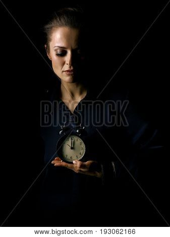 Coming out into the light. Portrait of woman in the dark dress isolated on black background showing alarm clock