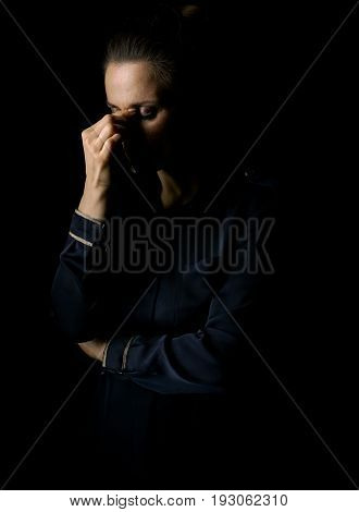 Coming out into the light. Portrait of stressed woman in the dark dress isolated on black