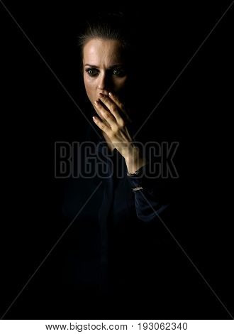 Coming out into the light. Portrait of stressed woman in the dark dress isolated on black background