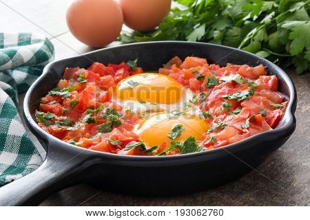 Shakshuka in iron frying pan on wooden table. Typical food in Israel.