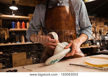 Cropped image of a shoemaker modeling design for a shoe at his workshop
