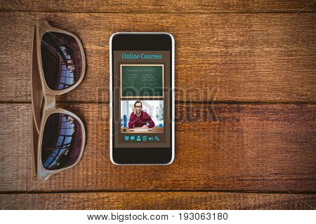 Computer generated image of e-learning interface against view of glasses and a smartphone