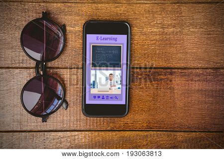 Digitally generated image of e-learning interface against view of glasses and a smartphone
