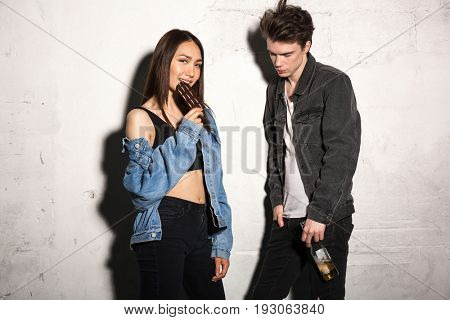 Image of young hipster man standing over gray background with beer near girlfriend eating chocolate.
