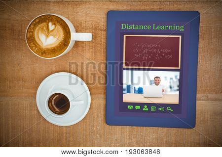 Digital image of e-learning interface against above view of coffee and a blue tablet