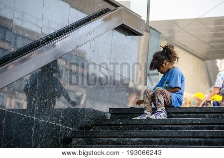 Homeless child eating on the stairway in the street. Social documentary street. September - 16. 2016. Novi Sad, Serbia. Editorial image.