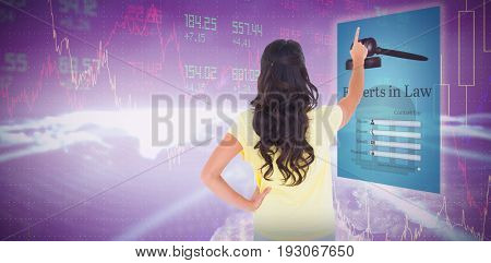 Brunette pointing in rear view against stocks and shares