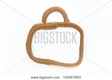 A shape of travel bag or suitcase drawn with fine sand on white background. A concept or idea.