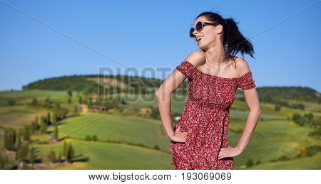 View of a girl in red dress in Tuscany hills, Italy