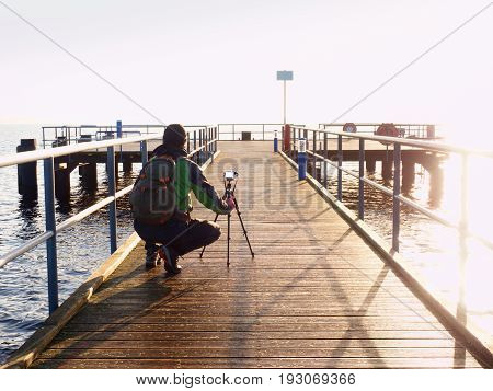 Alone Artist On Wooden Bridge. Photographer With Camera