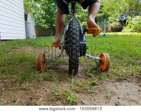 child peddling on bike with training wheels in dirt