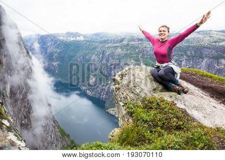 Happy people relax in cliff during trip Norway. Kjerag hiking route.