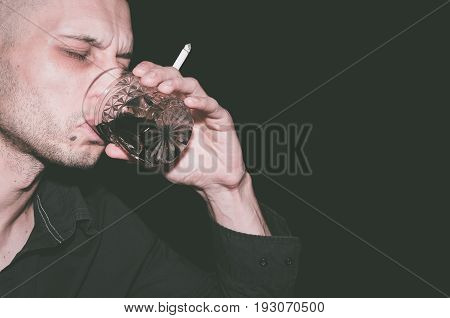 Alcohol and cigarettes. Drunk man drinking alcohol and smoke cigarette. Black background.