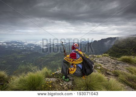 Gondar Ethiopia October 4th 2014: Mountain ranger with a gun resting and overlooking a valley in Simien Mountains