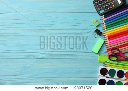 school and office supplies. school background. colored pencils, pen, pains, paper for  school and student education on blue wood background. top view with copy space
