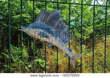 The Metal Ornament On A Balustrade In A Seaside Village, Symbolic In The Shape Of A Sawfish