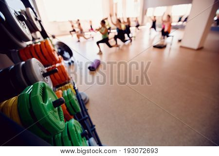 In the foreground a sports projectile disc for a bar in the background a group of girls of friends are engaged in fitness. Sports hall concept gym. Glare sun