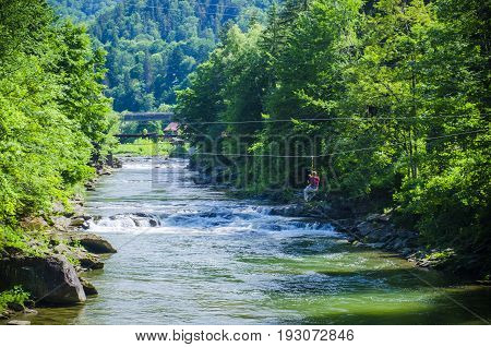 mountain river with a rapid current of rocks with a waterfall in summer