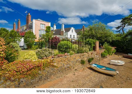 The shore of the Exe River at low tide. Boats aground.. Quite near the coastline are beautiful houses. Devon. England