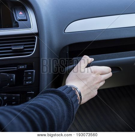 macro photo of a man's hand taking on glove compartment of cars