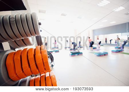 In the foreground a sports projectile disc for a bar, in the background a group of girls of friends are engaged in fitness. Sports hall concept gym. Glare sun