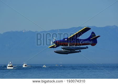 Victoria BC,Canada,August 4th 2014.A local float plane flies by fishing boats as it attempts to land on the water in Victoria BC.