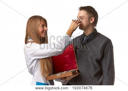 The beautiful  female oculist  checks sight at the patient on a white background.