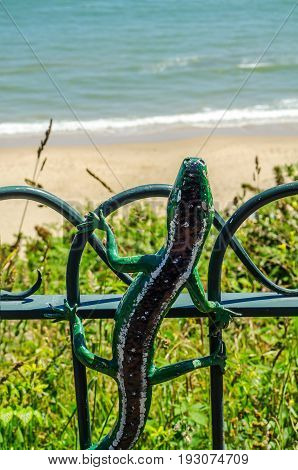 Metal Ornament On A Balustrade In A Seaside Village, Symbolic Lizard Shaped Element