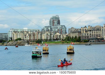 Victoria BC,Canada,August 16th 2014.Kayaks,water taxis and boats on the inner harbor with the Ocean Point Resort and Songhees in the background in Victoria BC.