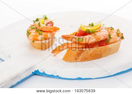 Shrimp snacks with bread on white wooden plate. Mediterranean seafood eating.