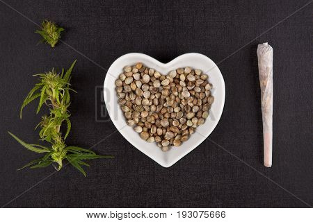 Healthy Marijuana medicine. Buds seeds in heart shaped bowl and cannabis joint from above on black background. I love alternative medicine.