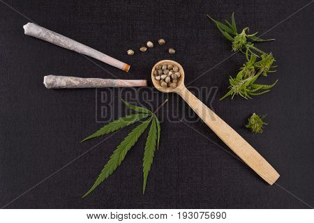 Marijuana seeds in wooden spoon with joints buds and leaves from above. Alternative medicine.