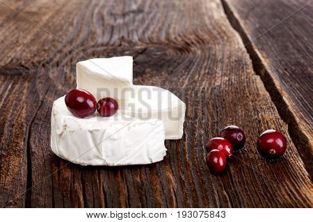 Delicious camembert cheese with cranberries on rustic wooden table.